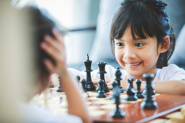 La ragazza asiatica da vicino sta giocando a un tavolo di scacchi