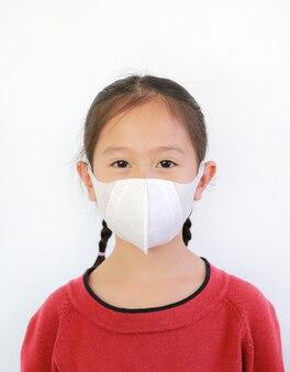 L'usura asiatica della bambina del primo piano protegge la maschera di protezione sopra bianco