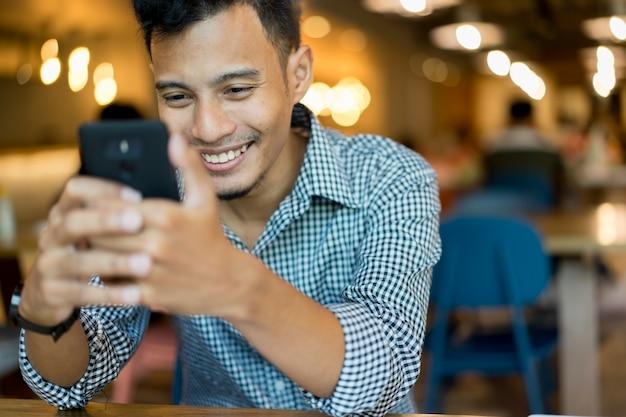 Chiuda sull'uomo asiatico che per mezzo del dispositivo mobile dello smart phone per gioco o comperando online