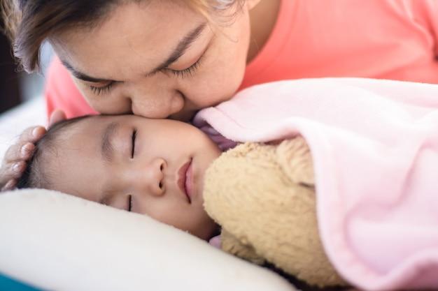 Chiuda sulla madre asiatica che bacia la sua neonata che dorme sul letto.