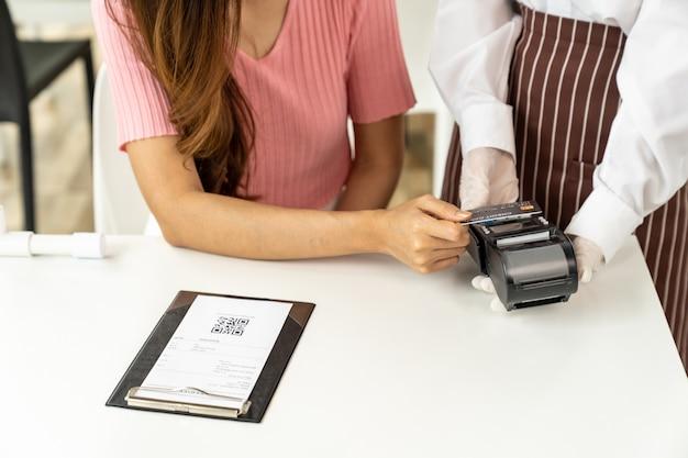 Close up donna asiatica cliente effettua il pagamento con carta di credito contactless