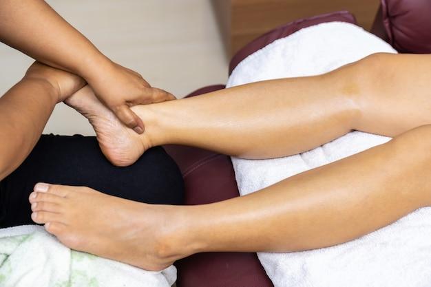Close up donna asiatica fare massaggio ai piedi a casa