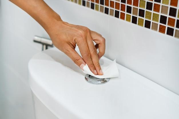 Chiuda in su della mano della donna asiatica utilizzando la toilette con sciacquone di carta bianca per prevenire il contatto diretto e prevenire infezioni, virus, batteri, batteri e sporco.