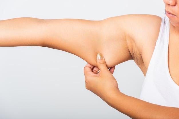 Chiuda su della donna asiatica che tira il grasso in eccesso su lei sotto il braccio, la pelle dell'ascella di problema, studio isolato su fondo bianco