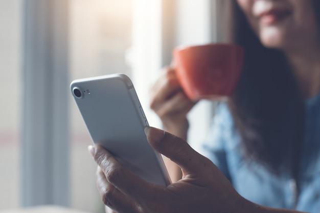 Primo piano di donna asiatica utilizzando il telefono cellulare e bere caffè