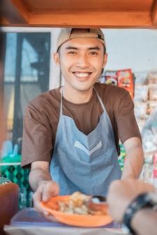 Chiuda sul venditore asiatico del giovane il negozio del carrello sorride quando serve i clienti alla bancarella del carrello