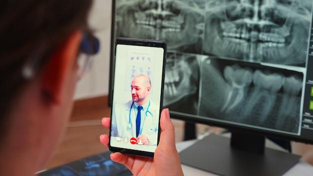 Primo piano dell'assistente che ha una videochiamata con uno stomatologo specialista che utilizza lo smartphone seduto nella moderna clinica dentale davanti al pc con radiografia digitale. medico di odontoiatria che spiega i sintomi del paziente