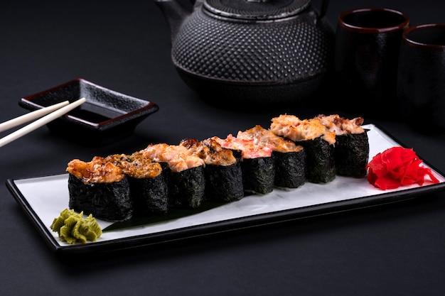 Primo piano di assortiti sushi al forno con salmone, gamberi, caviale, cozze, tonno, crema di formaggio e salsa piccante e bacchette