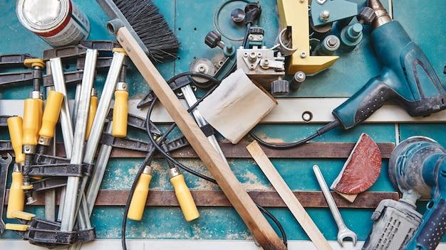Primo piano di strumenti assortiti per falegname sdraiato sulla superficie di lavoro blu. inquadratura orizzontale