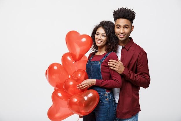 Chiuda sulle coppie afroamericane attraenti che abbracciano e che tengono il palloncino rosso del cuore.