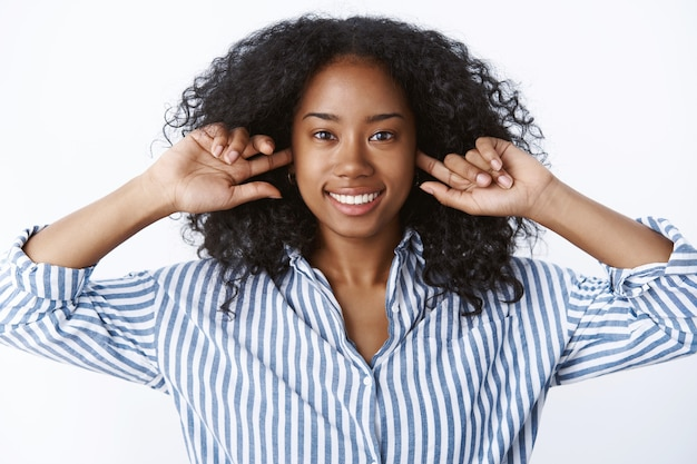 Close-up attraente sorridenti bella ragazza afroamericana taglio di capelli afro mettere le dita buchi per le orecchie non si sente riluttante ascoltare sorridendo gioiosamente rilassato umore spensierato indisturbato, muro bianco