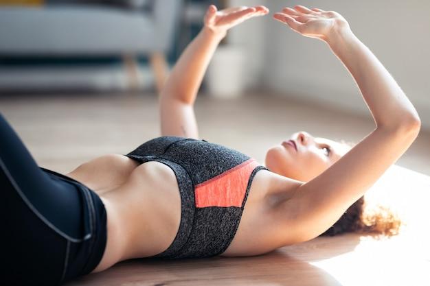 Primo piano di una giovane donna sportiva attraente che fa esercizi ipopressivi nel soggiorno di casa.