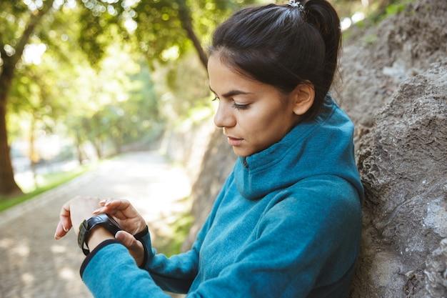 Primo piano di un attraente giovane donna fitness che indossa abbigliamento sportivo esercizio all'aperto, utilizzando smartwatch
