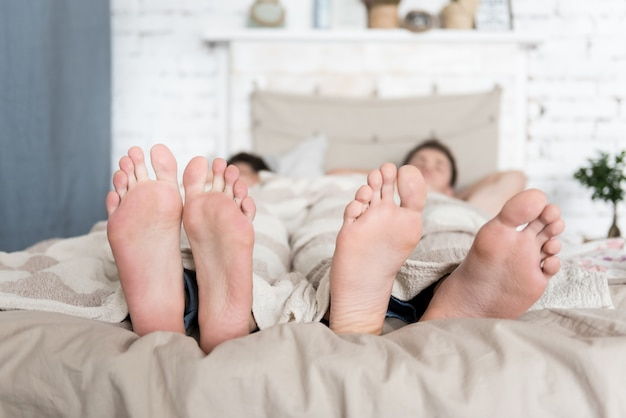 Chiuda in su dei piedi di giovani coppie gay attraenti a letto mentre dorme e trascorre la mattina a letto.