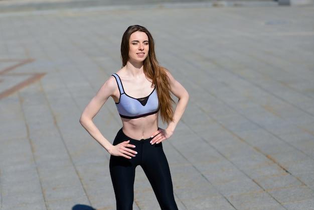 Un primo piano di una giovane donna attraente che corre, fa fitness all'aperto