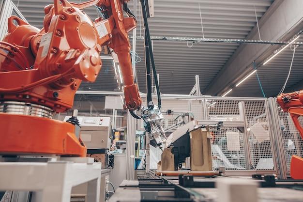 Primo piano di bracci robotici automatici nell'industria automobilistica, produzione in fabbrica di proiettori per automobili, concetto industriale