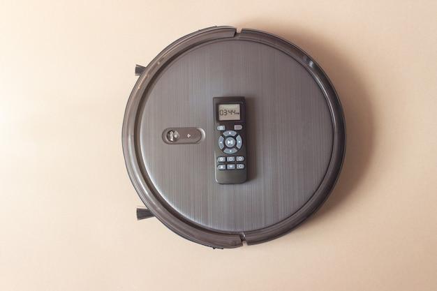 Primo piano del robot autonomo con telecomando su sfondo marrone. robot per la pulizia della casa.