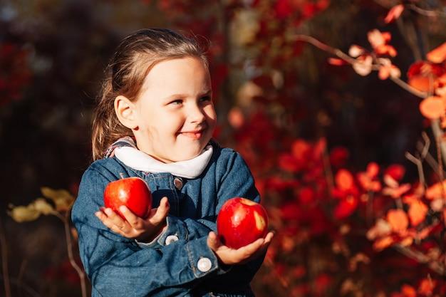 Close up raccolto autunnale concetto bella ragazza sorridente tenere grande mela rossa in mano incrociata con autunno...