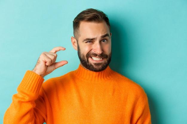 Primo piano di un uomo goffo che mostra piccolo o piccolo con le dita, in piedi dispiaciuto su sfondo azzurro.