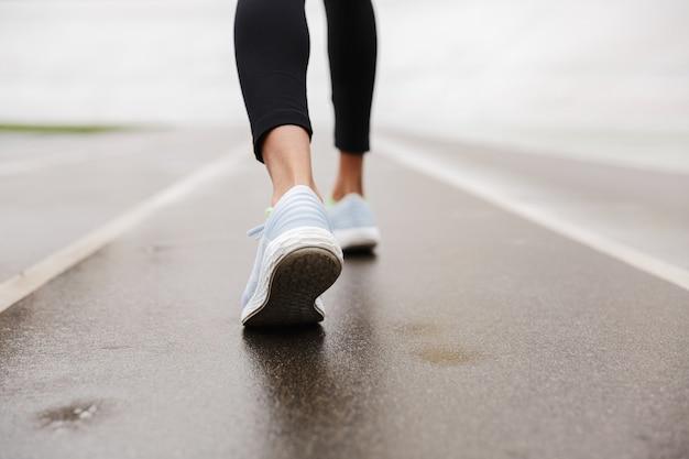 Vista ravvicinata di una scarpa da ginnastica da donna africana allo stadio, camminando