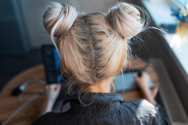 Vista posteriore ravvicinata di una giovane ragazza con due divertenti chignon per capelli, che lavora su laptop e tavoletta grafica.
