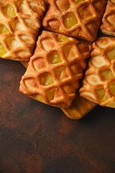 Primo piano sfondo di mini torte di pasta sfoglia fresca e croccante con ripieno di marmellata di pere e lime su uno sfondo strutturato nero e rosso scuro con fresco con fette di pera e lime, dall'alto, flatlay