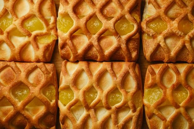 Primo piano sullo sfondo di mini torte di pasta sfoglia fresche e croccanti con ripieno di marmellata di pere e lime con fettine di pera e lime, vista orizzontale dall'alto, flatlay