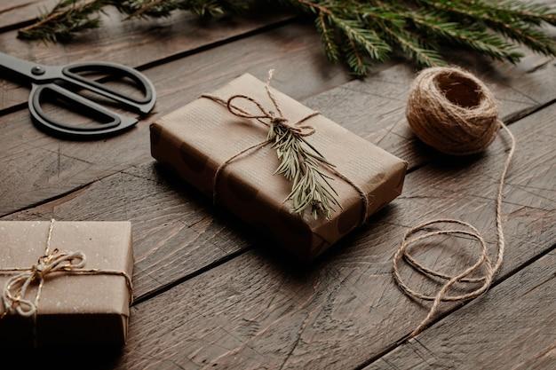 Immagine di sfondo ravvicinata di una confezione regalo di natale minimale avvolta in carta artigianale su tavola di legno copia ...