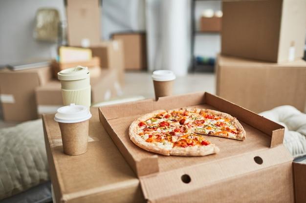 Chiuda sull'immagine di sfondo della pizza su una scatola di cartone come tavolo di fortuna in una stanza vuota mentre la fami...