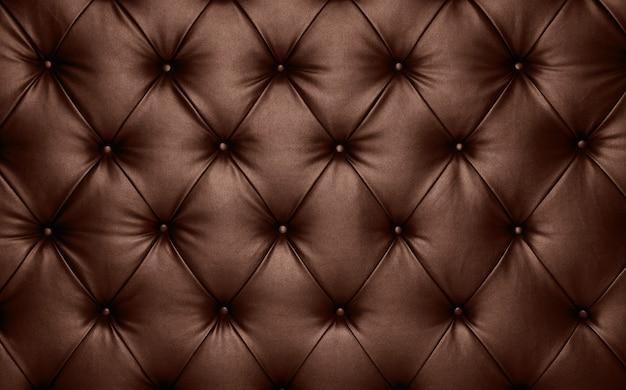 Close up texture di sfondo di marrone scuro capitone vera pelle, retro stile chesterfield morbido trapuntato mobili tappezzeria con profondo motivo a rombi e pulsanti