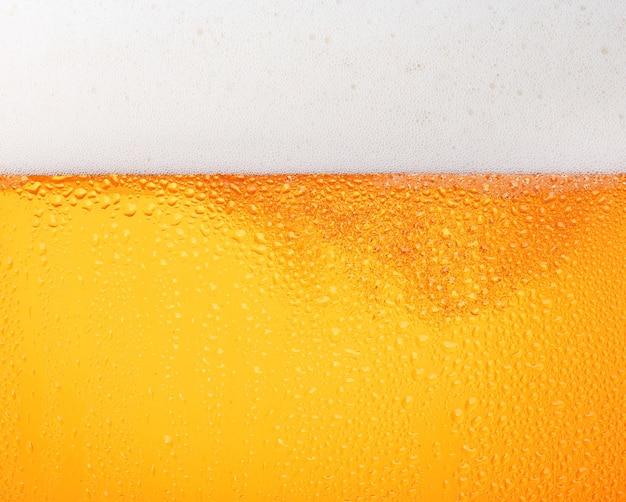 Close up texture di sfondo di versare birra lager con bolle e schiuma in un vetro gelido con gocce, vista laterale a basso angolo
