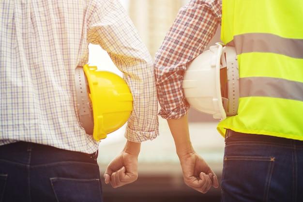 Chiuda sulla vista posteriore dell'operaio edile maschio di ingegneria che tiene il casco giallo di sicurezza e indossa indumenti riflettenti per la sicurezza dell'operazione di lavoro. esterno di edificio.