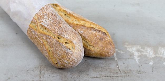 Close up baguette pane cotto su pietra grigia sfondo tavolo pane francese carta ecologica