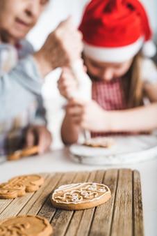 Primo piano di biscotti al forno decorare con crema su sfondo a natale