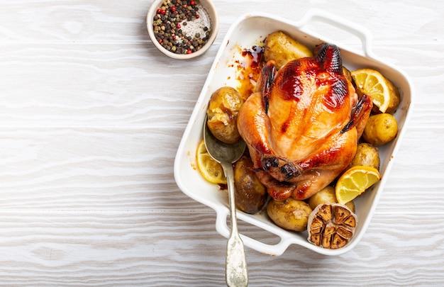 Primo piano di pollo biologico croccante intero al forno o arrosto con patate, aglio, limone in casseruola bianca con cucchiaio da portata su sfondo bianco in legno, vista dall'alto e spazio per il testo