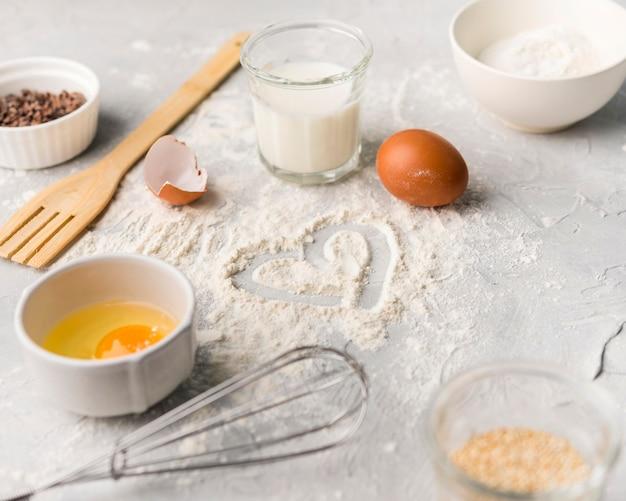 Farina di cottura del primo piano sulla tavola con le uova