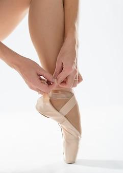 Primo piano della ballerina mette le scarpe da punta
