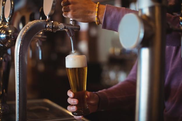 Primo piano della birra di riempimento dell'offerta della barra dalla pompa della barra