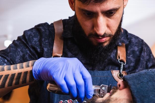 Chiuda in su del barbiere che taglia la barba di clienti nella bottega del barbiere