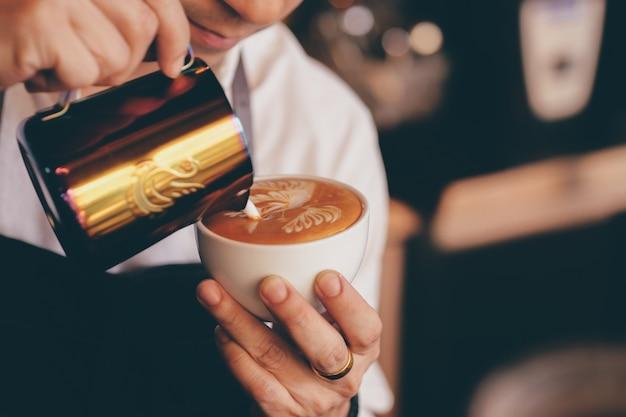 Chiuda sulla mano del barista che produce una tazza di caffè.