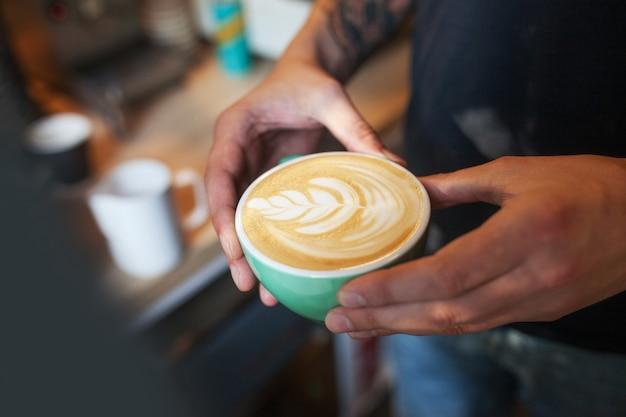 Chiuda in su del barista che tiene cappuccino aromatico. caffè pronto per la vendita. mani maschii che tengono una tazza di caffè.