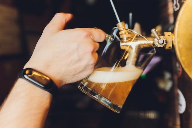 Primo piano della mano del barista al rubinetto della birra che versa una birra chiara alla spina.