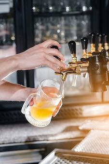 Primo piano del barista che riempie un boccale di birra leggera. il bancone del bar del pub.