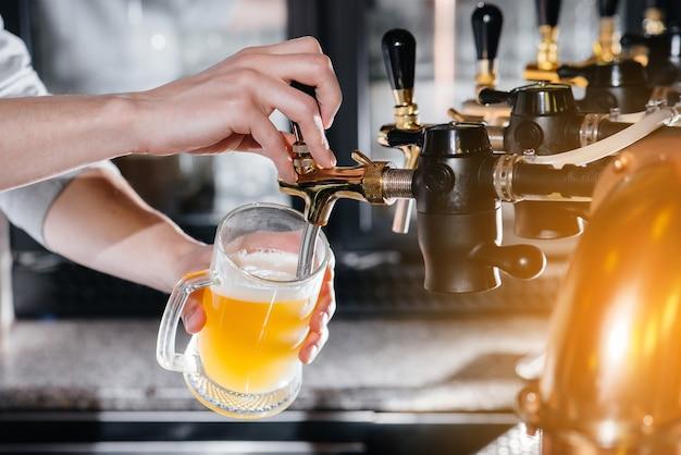 Primo piano del barista che riempie un boccale di birra leggera. il bancone del bar del pub. Foto Premium