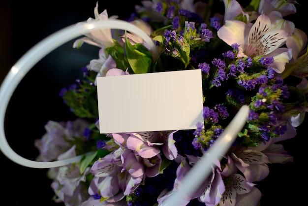 Cestino di primo piano con fiori di alstrameria e biglietto da visita con posto per il testo.