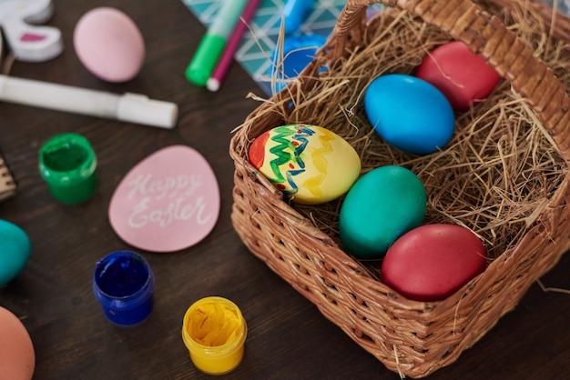 Primo piano del cesto con le uova dipinte di pasqua sul tavolo che si preparano per le vacanze