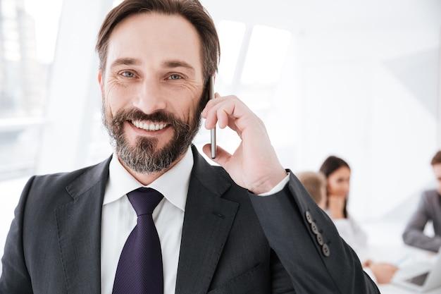 Primo piano barbuto uomo d'affari che parla al telefono in ufficio con i colleghi