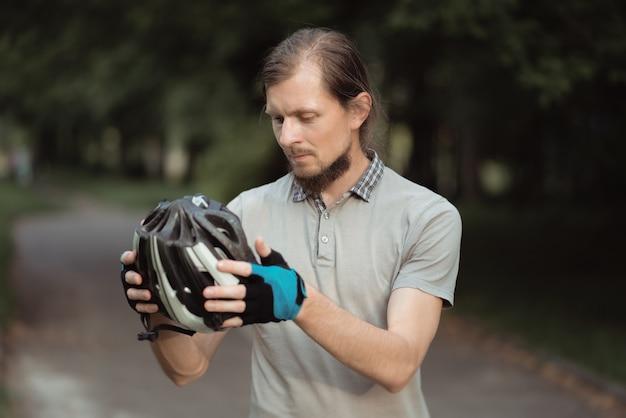 Primo piano di consegna barbuto uomo che indossa il casco in piedi con la bicicletta all'aperto, pronto per andare in bicicletta