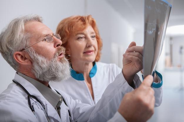Primo piano di un dottore maschio anziano con la barba, parlando con il suo collega di sesso femminile, guardando la risonanza magnetica di un paziente