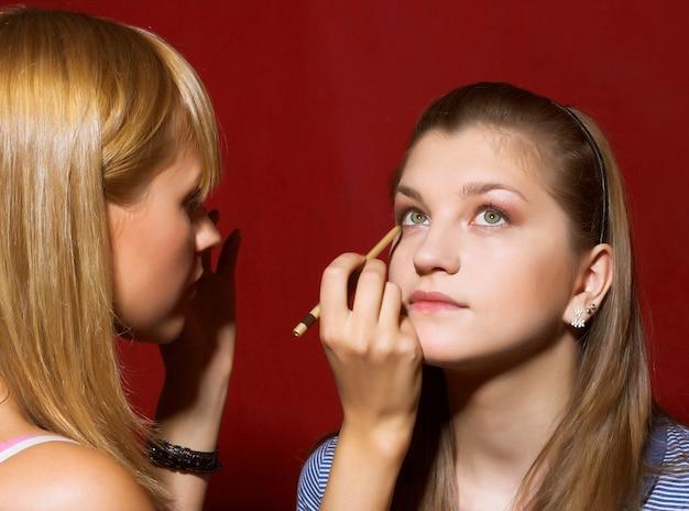 Chiuda in su dell'estetista che crea trucco per una giovane donna nel salone di bellezza.